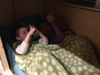 Arianna (8) plays shadow puppets with Caleb (3)